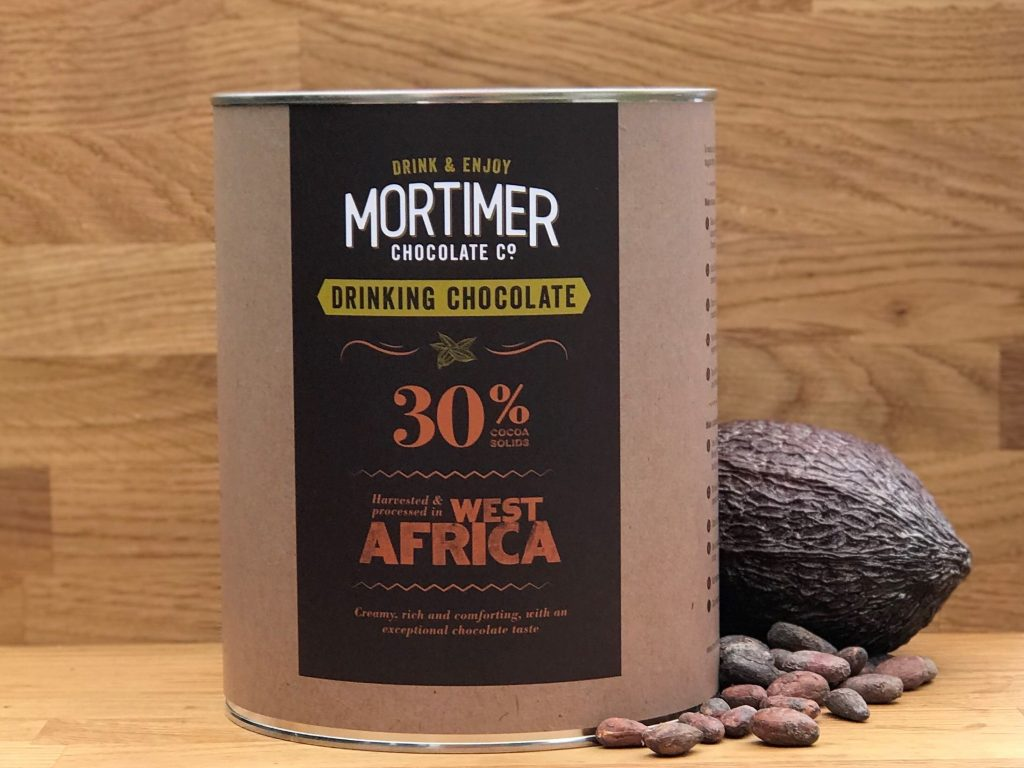 2 kg tin of 30% Drinking Chocolate sitting next to a cocoa pod and a sprinkling of cocoa beans