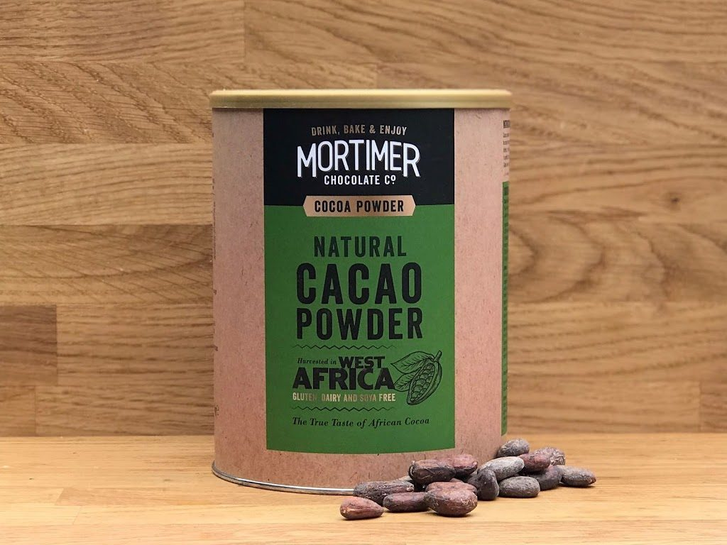 a lifestyle image of natural cacao powder with cocoa beans beside the product