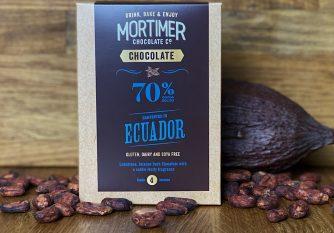 70% Ecuador Chocolate Powder as a lifestyle image with a cocoa pod and cocoa beans