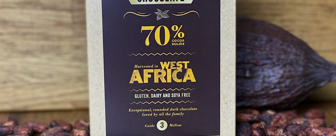 70% West African Chocolate Powder as a lifestyle image surrounded by cocoa beans and a cocoa pod