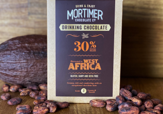 30% West African Drinking Chocolate as a lifestyle image surrounded by a cocoa pod and cocoa beans