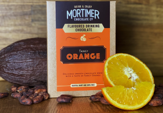 Mortimer Chocolate tangy orange drinking chocolate as a lifestyle image surrounded by oranges, cocoa pods an cocoa beans